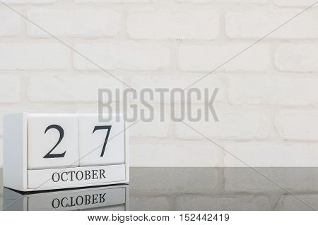 Closeup white wooden calendar with black 27 october word on black glass table and white brick wall textured background with copy space selective focus at the calendar