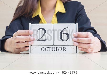 Closeup white wooden calendar with black 26 october word in blurred working woman hand on wood desk in office room selective focus at the calendar