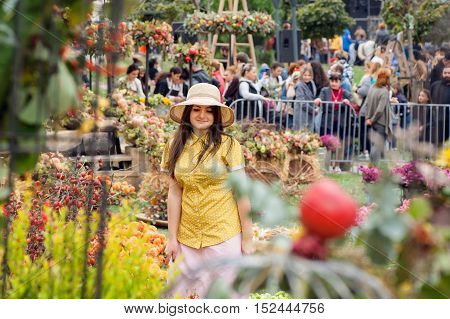 TBILISI, GEORGIA - OCT 16, 2016: Beautiful woman in hat walking at fruit garden of the annualy festival Tbilisoba on October 16, 2016. Tbilisoba is traditional festival in capital of Georgia from 1979