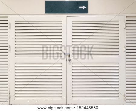 Closeup old white wooden door textured background with green tab tell the way in right