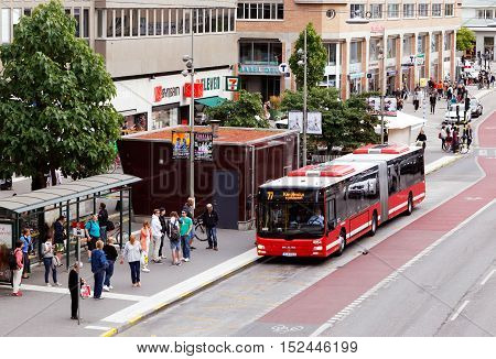 Stockholm, Sweden - August 31, 2015: Red bus in traffic for SL traffic on line 77 with the destination Karolinska Hospital arrives to stop Hornstull at the street Langholmsgatan where people are waiting.