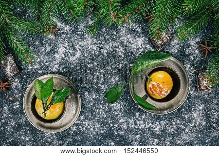 Coffee cups with mandarins inside over black surface covered with sugar powder and decorated with frame of evergreen twigs, chocolate and star anise
