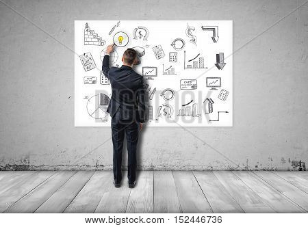 Back view of a businessman holding magnifier and seeing a glowing bulb on business sketches. Financial and business concept. Symbol of ideas. The way to wealth and success.