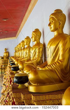 Golden Buddha sculptures sitting in a row