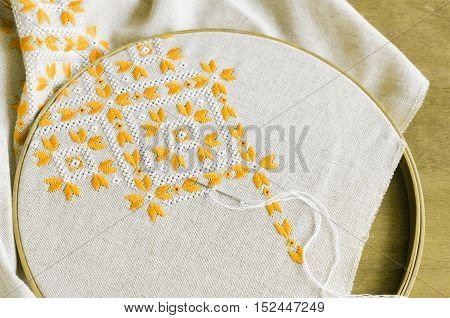 Element handmade embroidery on linen by yellow and white cotton threads. Craft embroidery. Design of ethnic pattern.