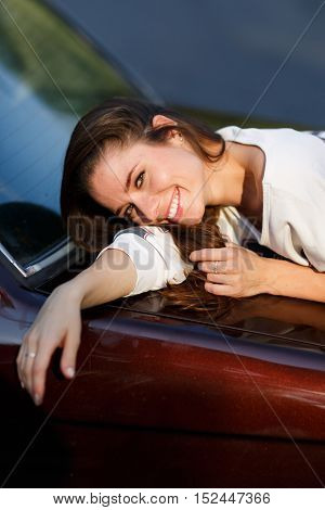 Outdoors portrait of smiling carefree young woman lying on hood of brown car