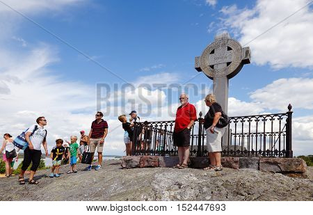 Bjorko, Sweden - July 19, 2014: People at Ansgar monument in the shape of a Celtic cross as the 1000 anniversary of the missionary Ansgar's arrival at Birka erected the cross in 1834 on Bjorko island Sweden.