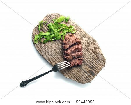 Sliced beef with fork and greenery on wood plate. Top view. Isolated on white. Path included
