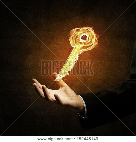 Close of businessman hand showing fire glowing key symbol