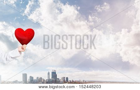 Close view of woman doctor against city background holding red heart