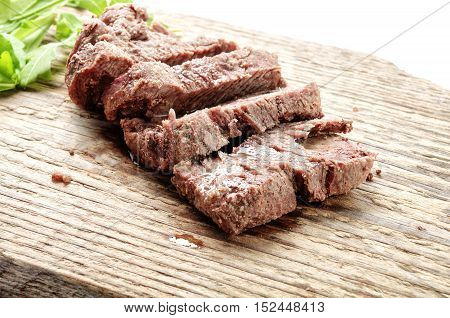 Slice of meat on wood board. Beef on table