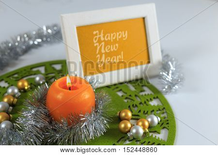 Happy New Year greeting card on green christmas mat silver tinsel with silver and golden christmas balls and orange candle against white background horizontal top view