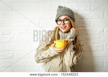 Happy Smiling Hipster Girl in Knitted Sweater and Beanie Hat with a Mug in Hands. Nice Shy Woman at White Brick Wall Background. Winter or Autumn Warming Up Concept. Toned Photo with Copy Space.