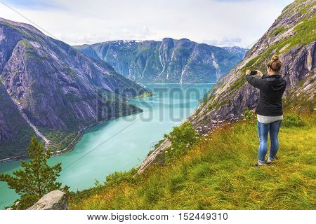 Woman hiking tourist in the high norwegian mountains over a beautiful fjord.