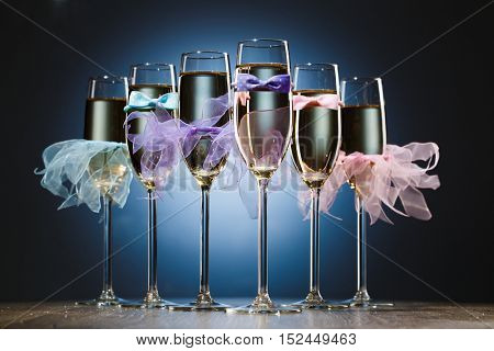 Set of glasses with champagne in colored dress newlyweds
