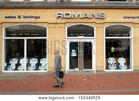 Reading, England - April 23, 2015: A pedestrian in a suit passes by the window display of Romans Estate Agents in Reading, a town in the South East of England