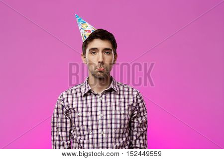 Upset handsome man looking at camera over purple background. Birthday party. Copy space.