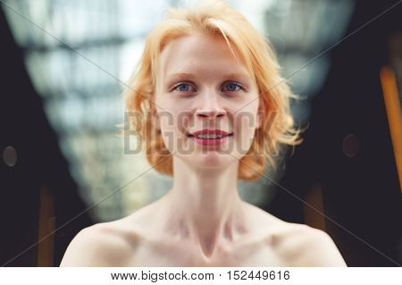 Smiling ginger woman close up on background of glass ceiling, tinted photo