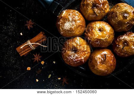 Apples baked with sugar, honey and spices, on dark wooden table. Top view, close view