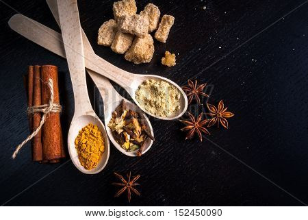 Ingredients for ginger biscuits, Christmas baking, and baking to the day of Thanksgiving: ginger, cinnamon, cardamom, citrus peel, anise. Top view, copy space