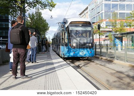 Stockholm, Sweden - May 13 ,2014: Passengers waiting at the tram stop Martensdal when the tram in service of SL Tvarbanan arrives towards Alvik.