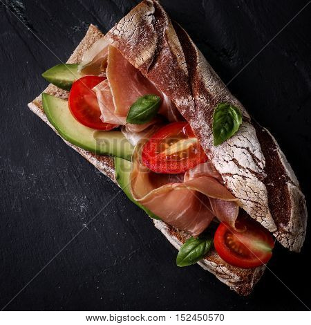 Ciabatta Sandwich With Prosciutto,avocado,cherry Tomatoes And Basil On Dark Background