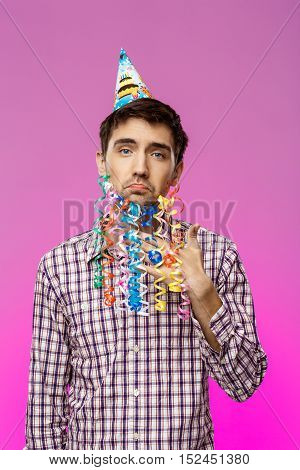 Young handsome man with fake beard posing at birthday party over purple background. Copy space.