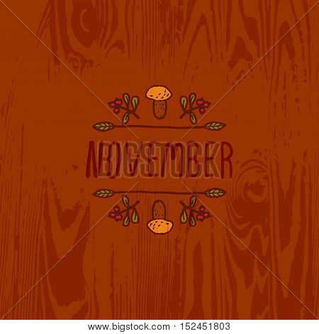Hand-sketched typographic element with mushroom, berries and text on wooden background. November