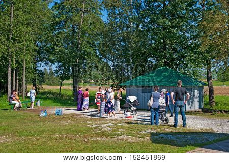 KUREMAE, IDA-VIRUMAA COUNTY, ESTONIA - AUGUST 21, 2016: Pilgrims near baptistery with The Holy Spring water on the place of Marian apparition. Located not far from Puhtitsa Orthodox Dormition Convent