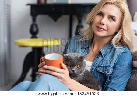 Best friends. Young pretty blond lady sitting and home and holding her favorite cat and cup.