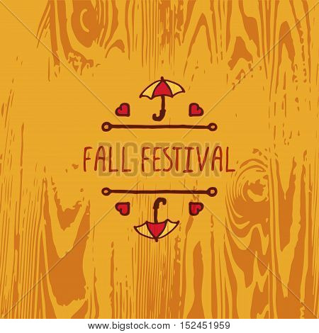 Hand-sketched typographic element with umbrella, hearts and text on wooden background. Fall festival