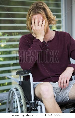 young man sitting in wheel chair looking desperate