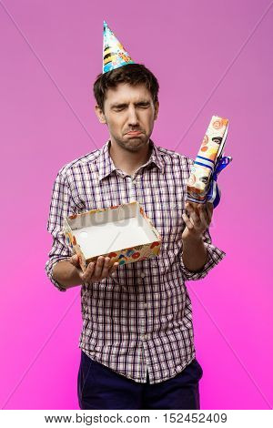 Sad young handsome man opening birthday gift over purple background. Copy space.