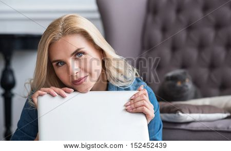 Fell in love. Young blond haired woman covered with her modern laptop and dreamy looking forward.