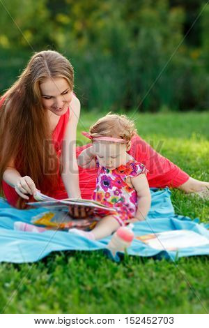 Mum with small daughter looking at book sitting on blanket in park