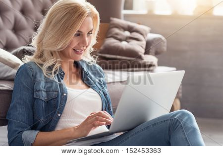 Good news. Young smiling blond woman sitting on floor behind grey couch and using modern laptop.