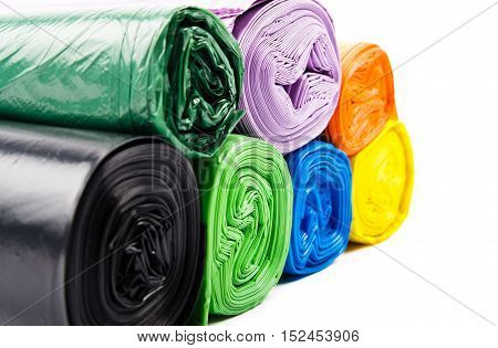 Seven colored garbage bags on white background