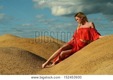 The beautiful girl in a red dress in sand