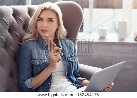 Getting idea. Young thoughtful pretty blond lady sitting on big grey couch with white laptop, and holding pencil on her mouth.