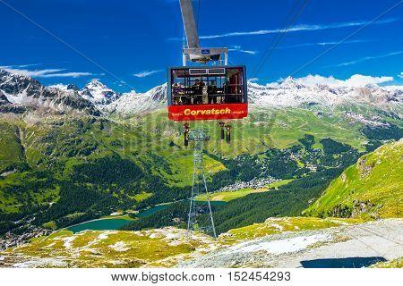 SANKT MORITZ, SWITZERLAND - JULY 14 2016: People in Corvatsch cable car enjoying the stunning view of lake Sils Silvaplana in Upper Engadin valley near Sankt Moritz Grisons Switzerland Europe.