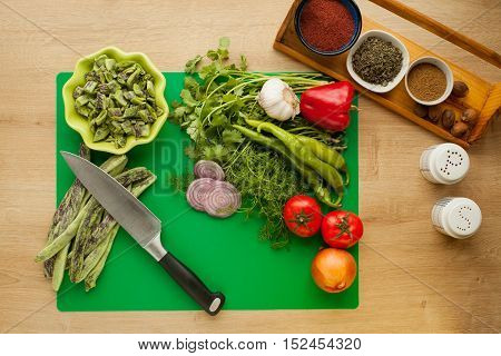 Fresh vegetables prepared for cooking, vegan meal, green beans. Menu for healthy lifestyle, ingredients for cooking salad with spices in kitchen with knife for cutting food.