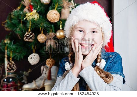 Festive little girl smiling at camera against home with christmas tree. Holding hands on cheeks