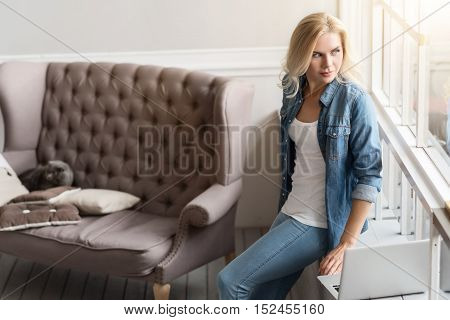 What nice weather. Portrait of nice blond lady leaning on windowsill at home and looking through window.