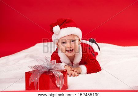 Beautiful little baby celebrates Christmas. New Year's holidays. Baby in a Christmas costume with gift.