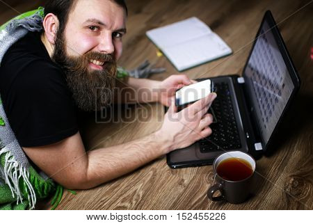 bearded handsome man lies on the floor wrapped in a plaid, and working at a laptop