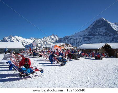 GRINDELWALD, SWITZERLAND - 3 MARCH 2016: People relaxing and enjoying the sun after skiing on Männlichen Jungraujoch ski region Switzerland Europe