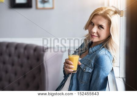 Healthy eating. Close up portrait of young happy blond woman leaning on window and holding glass with freshly made juice.