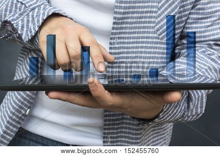 Business person analyzing financial statistics displayed on the tablet screen. Selective focus.