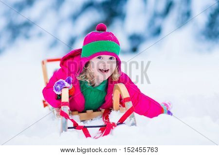 Little girl enjoying a sleigh ride. Child sledding. Toddler kid riding a sledge. Children play outdoors in snow. Kids sled in the Alps mountains in winter. Outdoor fun for family Christmas vacation.