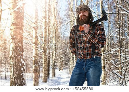 bearded handsome man went into the forest with an ax to produce wood for the furnace